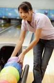 Woman selecting ball at bowling alley - Asia Images Group