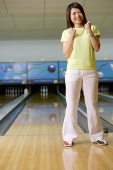 Woman standing at bowling alley, hands in fists, smiling - Asia Images Group
