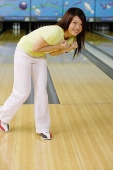 Woman at bowling alley, bending over smiling - Asia Images Group