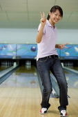 Woman at bowling alley, smiling, making peace sign - Asia Images Group
