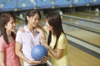 Women at bowling alley, talking - Asia Images Group