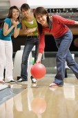 Woman bowling, friends watching her - Asia Images Group