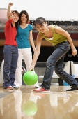 Woman bowling, friends watching her in the background - Asia Images Group
