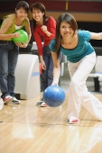 Woman bowling, friends behind her, watching - Asia Images Group