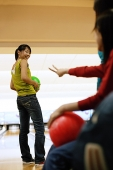 Three women at a bowling alley, one woman with bowling ball, looking over shoulder - Asia Images Group