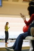 Woman at bowling alley, turning to look at friends behind her - Asia Images Group