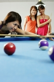 Woman holding pool cue, aiming, women watching in the background - Asia Images Group