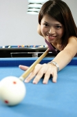 Woman with pool cue, aiming at ball - Asia Images Group