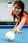 Woman in orange top, holding pool cue, aiming at ball - Asia Images Group