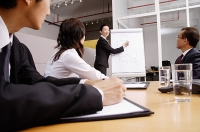Group having a business meeting, woman writing on flipchart - Asia Images Group