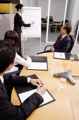 Business people in meeting, woman writing on flipchart - Asia Images Group