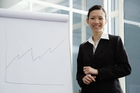 Businesswoman standing next to flipchart, smiling at camera - Asia Images Group
