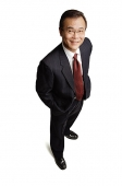 Businessman standing with hands in pocket, smiling at camera - Asia Images Group