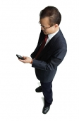 Businessman standing, looking at mobile phone - Asia Images Group