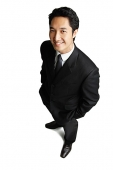 Businessman standing with hands in pockets, smiling at camera - Asia Images Group