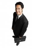 Businessman with briefcase, smiling at camera - Asia Images Group