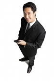 Businessman holding mobile phone, smiling at camera - Asia Images Group