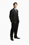 Businessman standing, hands in pocket - Asia Images Group