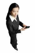 Businesswoman holding mobile phone, looking at camera - Asia Images Group