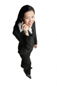 Businesswoman using mobile phone, looking at camera - Asia Images Group
