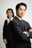 Businessman with arms crossed, woman in the  background - Asia Images Group