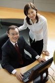 Businessman and woman in office cubicle, looking up at camera - Asia Images Group