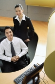 Businessman and woman in office cubicle, smiling at camera - Asia Images Group