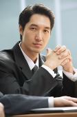 Businessman looking at camera, hands clasped - Asia Images Group