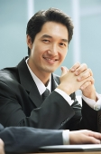 Businessman smiling at camera, hands clasped - Asia Images Group