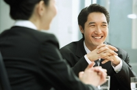 Businessman smiling, hands clasped, woman in the foreground - Asia Images Group