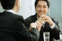 Businessman smiling, at woman in front of him - Asia Images Group