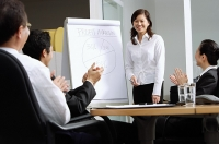 Businesswoman standing next to flipchart, colleagues sitting and clapping - Asia Images Group