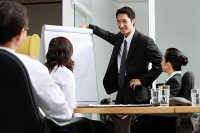Group having a business meeting, man standing next to flipchart - Asia Images Group