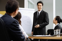 Executives having a business meeting, man giving presentation - Asia Images Group