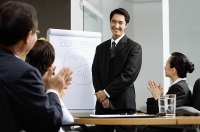 Businessman standing next to flipchart, other executives clapping - Asia Images Group