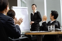 Businesswoman standing next to flipchart, other executives clapping - Asia Images Group