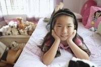 Girl in bedroom, lying on bed, hands on chin, looking at camera - Asia Images Group