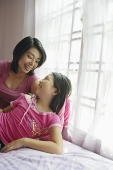 Mother and daughter at home, looking at each other - Asia Images Group