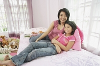 Mother and daughter in bedroom, side by side, looking at camera - Asia Images Group