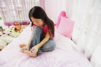 Girl in bedroom, painting toenails - Asia Images Group