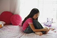 Girl in bedroom, painting toenails, side view - Asia Images Group