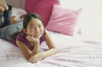 Girl lying on bed, hands on chin, smiling at camera - Asia Images Group