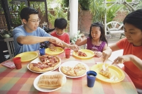 Family of four having pizza on patio - Asia Images Group
