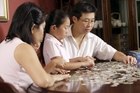 Family of four fixing jigsaw puzzle on coffee table - Asia Images Group