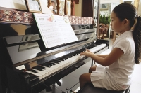 Girl at home, playing piano - Asia Images Group