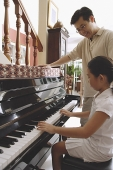 Father watching daughter playing the piano - Asia Images Group