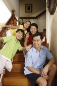 Family with two children, sitting on stairs, smiling at camera - Asia Images Group