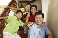 Family with two children, sitting on stairs, smiling at camera, portrait - Asia Images Group