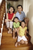 Family sitting on stairs, smiling at camera, portrait - Asia Images Group
