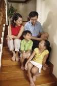 Family sitting on stairs, looking at each other - Asia Images Group